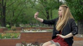 美丽的白肤金发的女孩在做在智能手机的公园selfie 摆在为selfie的女孩 股票视频