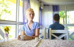 美丽的白肤金发的女孩在咖啡馆坐在桌上,拿着杯子 免版税图库摄影