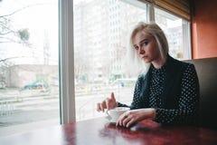 年轻美丽的白肤金发的女孩在咖啡馆的黑开会穿戴了与一个杯子热的咖啡 库存图片