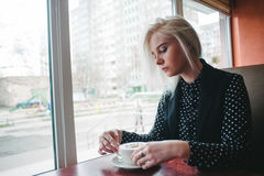 年轻美丽的白肤金发的女孩在咖啡馆的黑开会穿戴了与一个杯子热的饮料 在咖啡馆的早餐 免版税图库摄影
