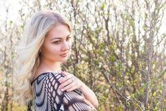 美丽的白肤金发的女孩在春天樱桃庭院里 库存图片