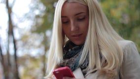 年轻美丽的白肤金发的女孩在有一个电话的秋天公园在手上 股票录像