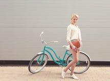 美丽的白肤金发的女孩在有棕色葡萄酒袋子的葡萄酒自行车附近站立有的乐趣和看好的心情秘密审议和smi 免版税库存图片