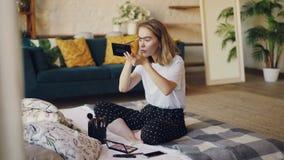 美丽的白肤金发的女孩在构成有刷子和化妆用品成套工具的绘画眼眉投入在家坐床 beauvoir 影视素材