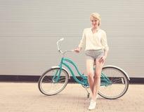 美丽的白肤金发的女孩在葡萄酒自行车附近站立有的乐趣和看好的心情秘密审议和微笑,温暖, tonning 免版税图库摄影