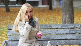 年轻美丽的白肤金发的女孩坐一条长凳在有一个电话的秋天公园在手上 影视素材
