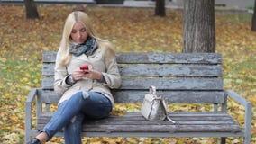 年轻美丽的白肤金发的女孩坐一条长凳在有一个电话的秋天公园在手上 股票录像