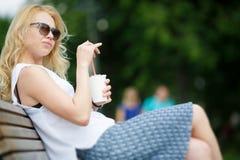 美丽的白肤金发的女孩坐与杯子的长凳饮料 免版税图库摄影
