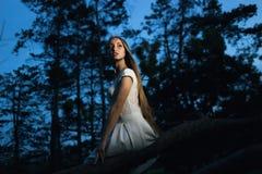 美丽的白肤金发的女孩坐老树枝在神秘的神仙的夜森林里 免版税库存图片