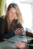美丽的白肤金发的女孩愉快微笑的坐在看片剂个人计算机计算机,在桌上的手机的咖啡店或餐馆 免版税库存照片