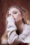 年轻美丽的白肤金发的女孩是哀伤的 免版税库存图片