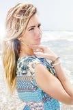 美丽的白肤金发的女孩有海背景 甜态度 免版税库存照片