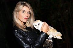 美丽的白肤金发的女孩爱抚谷仓猫头鹰 免版税库存照片
