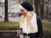 美丽的白肤金发的女孩用咖啡 免版税库存照片
