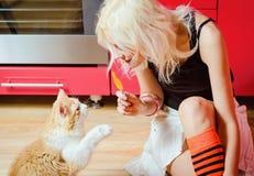 美丽的白肤金发的女孩用糖果在手中和猫坐厨房地板 库存图片