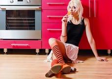 美丽的白肤金发的女孩用糖果在手中坐厨房地板 免版税库存图片