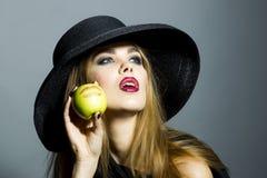 美丽的白肤金发的女孩用苹果 库存图片