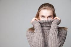 美丽的白肤金发的女孩穿冬天套头衫 图库摄影