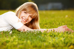 美丽的白肤金发的女孩草 库存照片