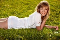 美丽的白肤金发的女孩草 库存图片