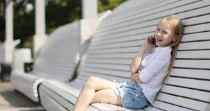 美丽的白肤金发的女孩谈话在一个手机在夏天公园 股票视频