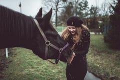 美丽的白肤金发的女孩从手喂养一匹大棕色马 免版税图库摄影