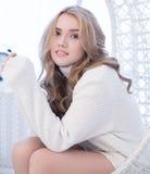 美丽的白肤金发的女孩画象套头衫的 库存图片