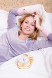 美丽的白肤金发的女孩画象有闹钟的有乐趣放松在白色床上的愉快的微笑的&看的照相机 库存图片