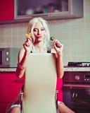 美丽的白肤金发的女孩画象用两个糖果在手上 库存图片