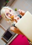 美丽的白肤金发的女孩画象用两个糖果在手上 免版税库存图片