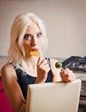 美丽的白肤金发的女孩画象用两个糖果在手上 免版税图库摄影
