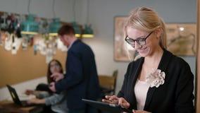 年轻美丽的白肤金发的女实业家在现代起始的办公室使用触摸屏幕片剂 缓慢的mo, Steadicam射击 影视素材