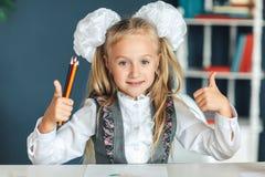 美丽的白肤金发的女小学生,有长,整洁地结辨的猪尾的 在一件白色女衬衫和果冻 她显示她的拇指和举行 库存照片