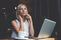 美丽的白肤金发的女性拜访的手机,当休息在便携式计算机上时的工作以后 库存图片
