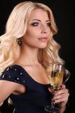 美丽的白肤金发的女服庄重装束,与杯香槟 免版税库存照片