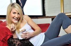 美丽的白肤金发的奶油色享用的冰妇女 免版税库存照片