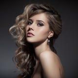 美丽的白肤金发的妇女。卷曲长的头发 图库摄影