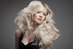 美丽的白肤金发的妇女。卷曲长的头发 免版税库存照片