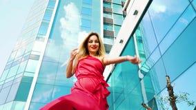美丽的白肤金发的妇女低角度射击通过摩天大楼的红色礼服的 影视素材