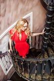 美丽的白肤金发的妇女佩带的时尚红色礼服 库存图片