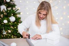 美丽的白肤金发的妇女包装的礼物在有Christma的客厅 图库摄影