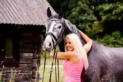 美丽的白肤金发的妇女和她的马在乡区 免版税库存照片