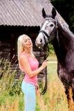 美丽的白肤金发的妇女和她的马在乡区 免版税库存图片