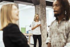 美丽的白肤金发的妇女在使用电话的办公室 免版税库存照片