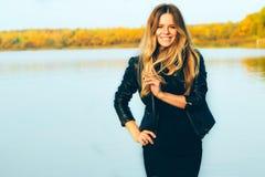 年轻美丽的白肤金发的妇女在有湖的秋天公园黑暗的在日落期间的皮夹克微笑完善的牙的 库存图片