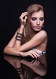 年轻美丽的白肤金发的妇女在镜子桌上坐黑ba 图库摄影