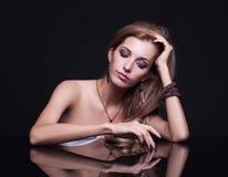 年轻美丽的白肤金发的妇女在镜子桌上坐黑ba 免版税库存图片