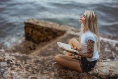 美丽的白肤金发的妇女坐一个石堤防和读书 被刺字的手 现代,时髦,学生 免版税库存照片