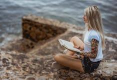 美丽的白肤金发的妇女坐一个石堤防和读书 被刺字的手 现代,时髦,学生 图库摄影