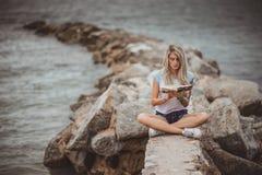 美丽的白肤金发的妇女坐一个石堤防和读书 被刺字的手 现代,时髦,学生 免版税库存图片